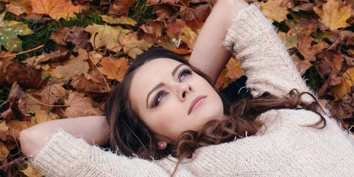 A young woman lying on top of leaves.