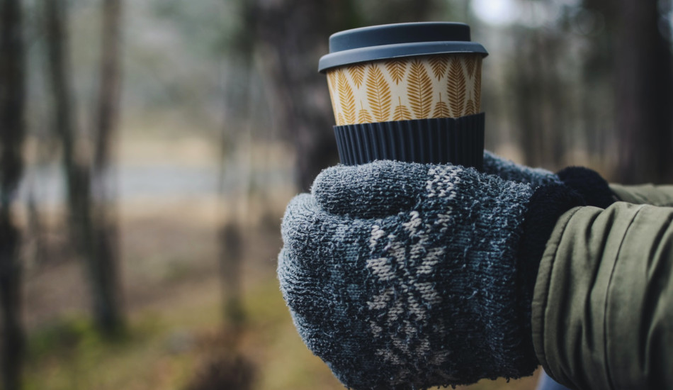 Closeup of someone holding an insulated cup in gloved hands.