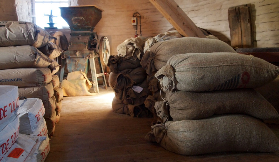 Sacks of grain stacked up inside a mill.
