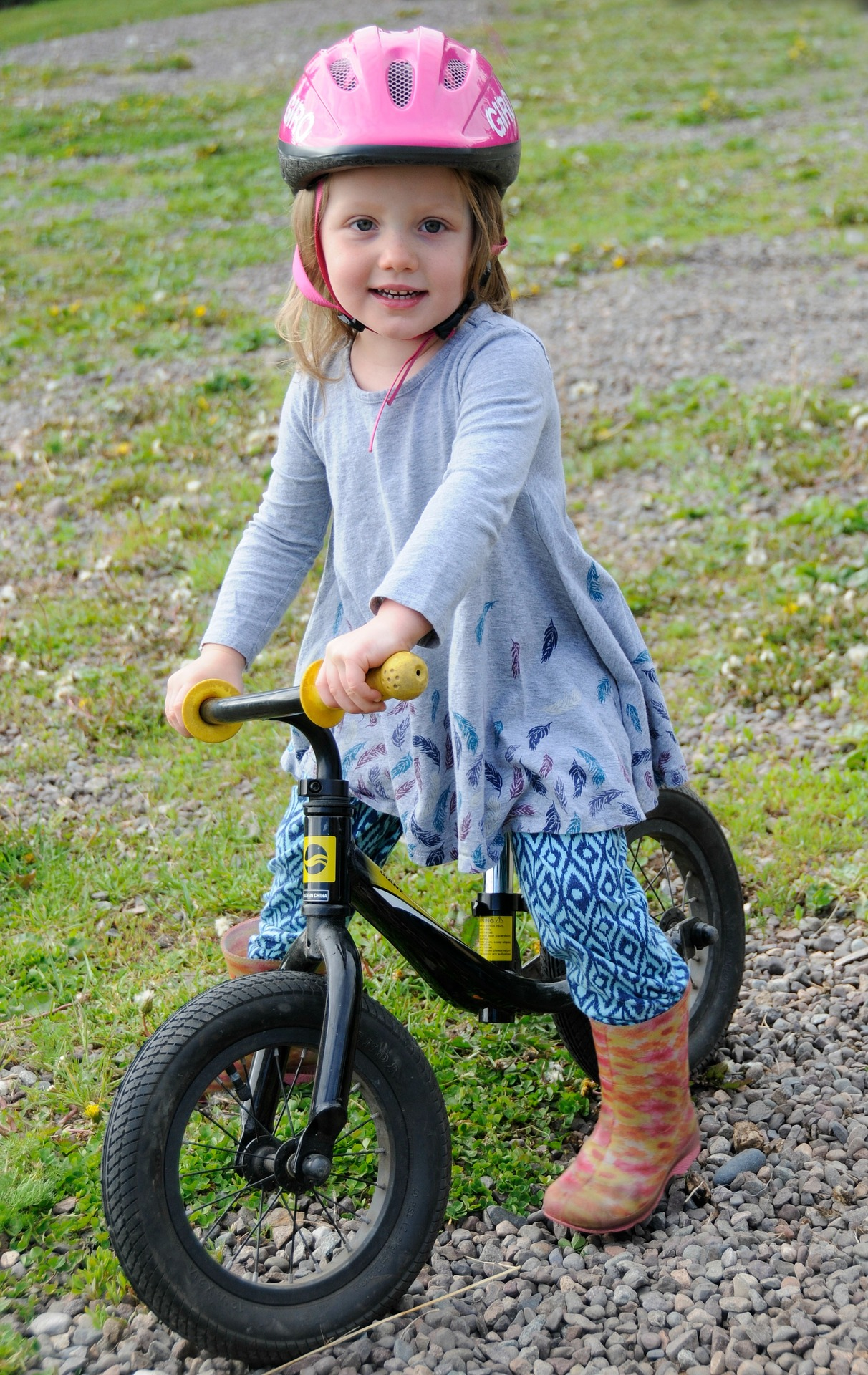 A girl poses with her balance bike.