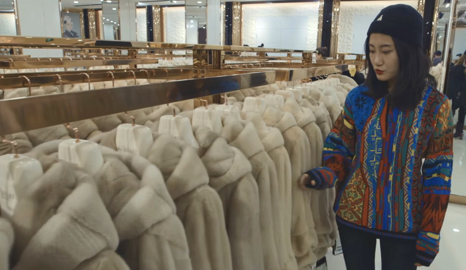 Chinese woman browses through a rack of mink coats.