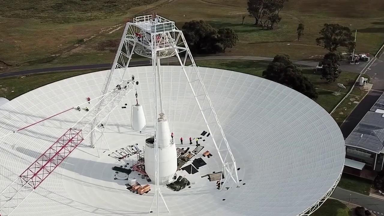 Crews conduct critical upgrades and repairs to the 70-meter-wide (230-foot-wide) radio antenna Deep Space Station 43 in Canberra, Australia. In this clip, one of the antenna's white feed cones (which house portions of the antenna receivers) is being moved by a crane. (Credit: CSIRO)