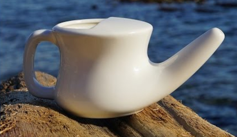 Close up of a white neti pot sitting on a rock by the ocean.