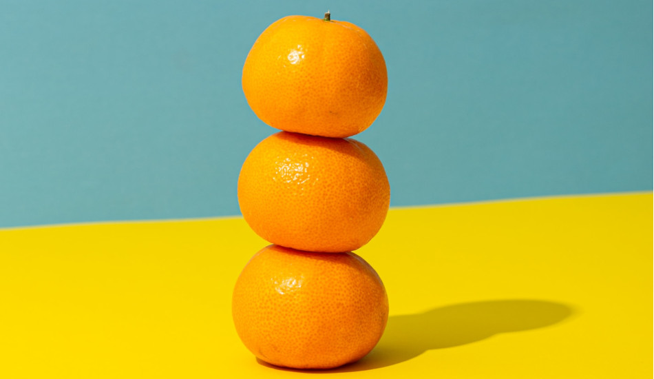 Three oranges stacked on a yellow countertop.