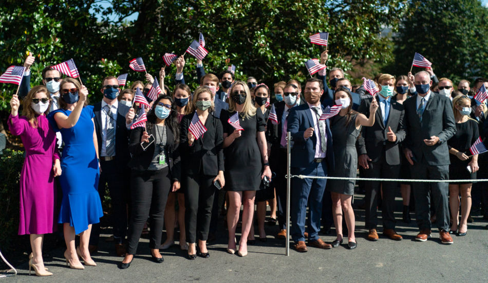 A group of people waving American flags.