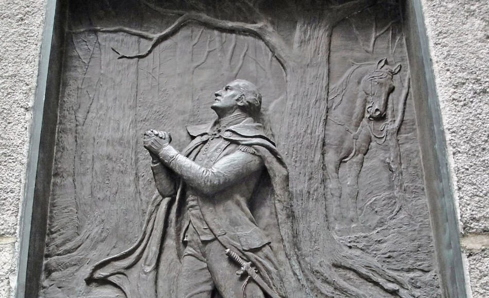 A brass relief of George Washington kneeling in prayer at Federal Hall in New York City.