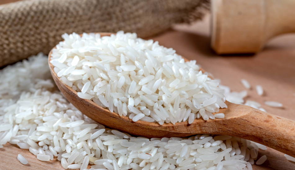 Dry white long rice in wooden spoon.