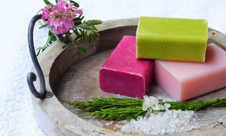 Three brightly colored bars of soap sitting in a dish.
