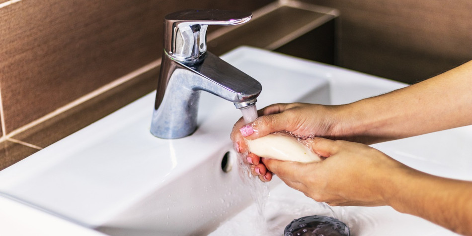 A woman washes her hands.