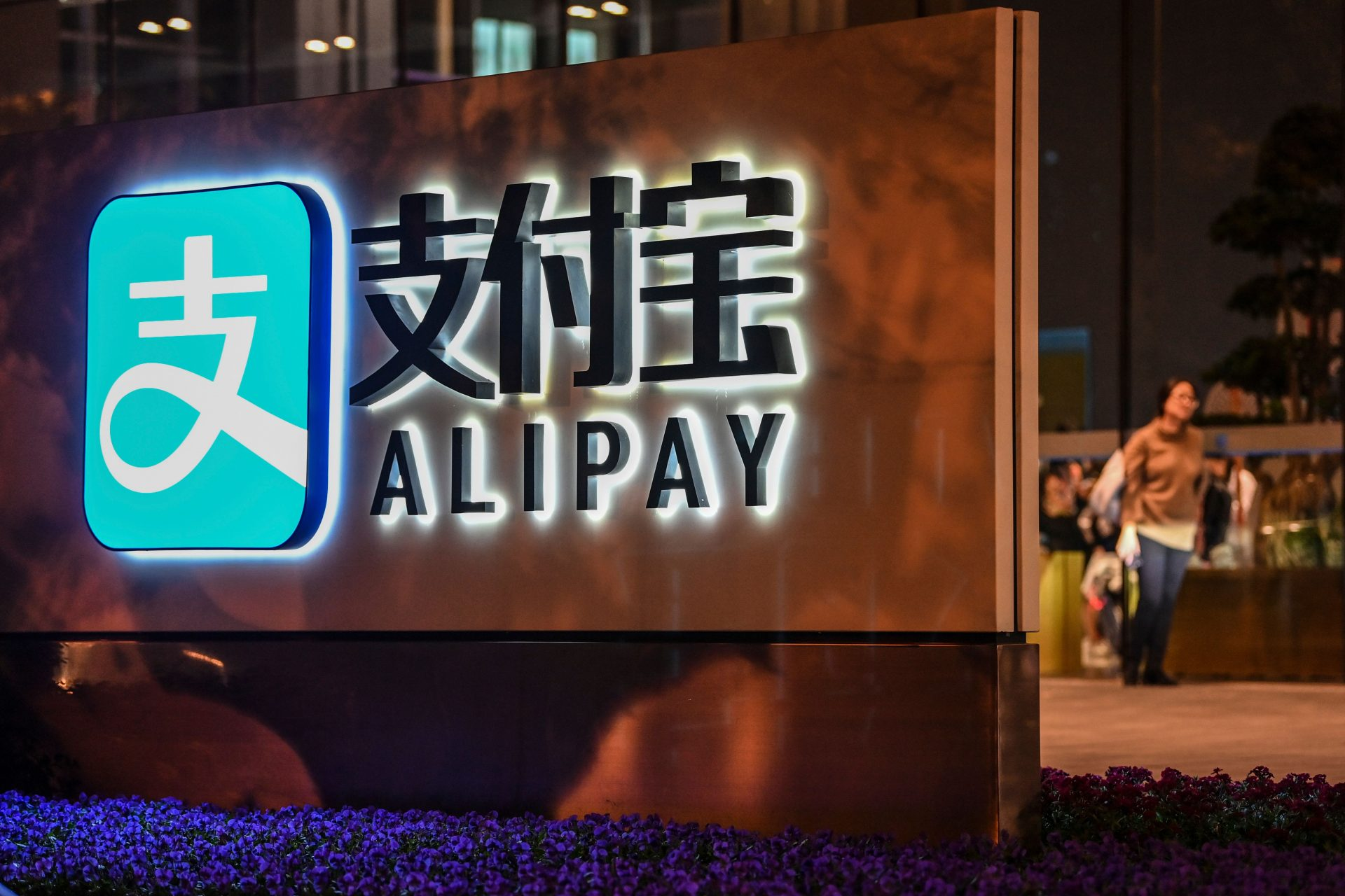 An Alipay logo is seen next to the Shanghai office building of its parent company, the Ant Group, in Shanghai on November 3, 2020. Jack Ma is the Chinese entrepreneur who runs these companies.