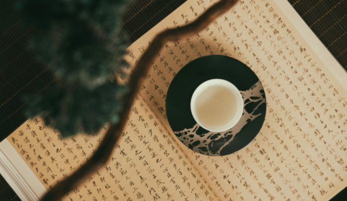 A cup sits on an open book containing Chinese writing.