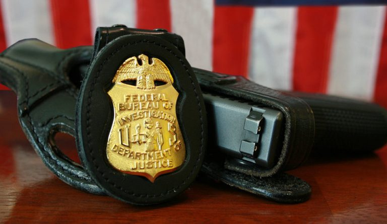 FBI badge and gun sitting on a table in front of the U.S. flag.