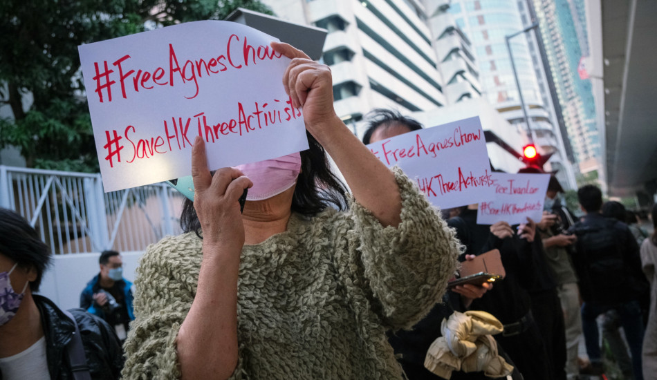 Hong Kong citizens hold signs calling for the release of Agnes Chow, one of the protesters sentenced to prison on charges of inciting, organizing, and participating in unauthorized assemblies.