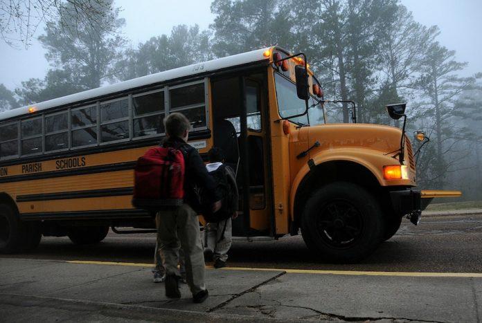 Children getting on a school bus.