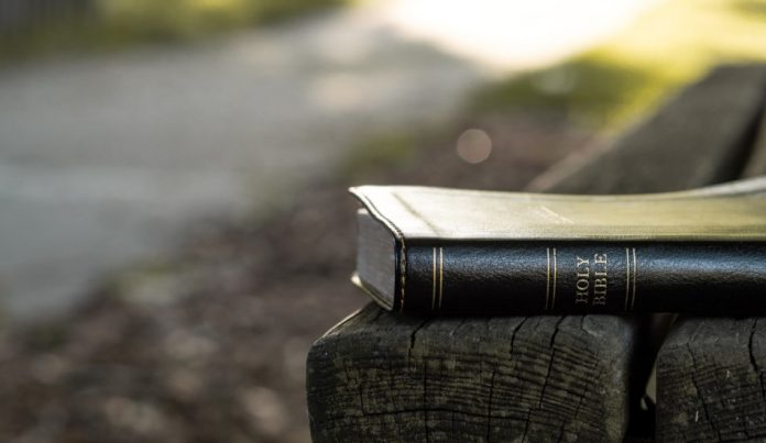 A Bible sitting on a park bench.