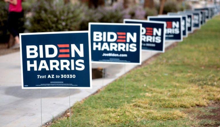Signs for Joe Biden line a sidewalk.