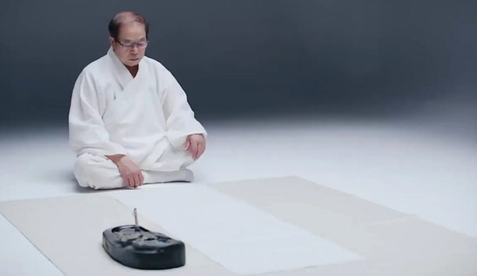 Liu Xitong sits with paper and ink.
