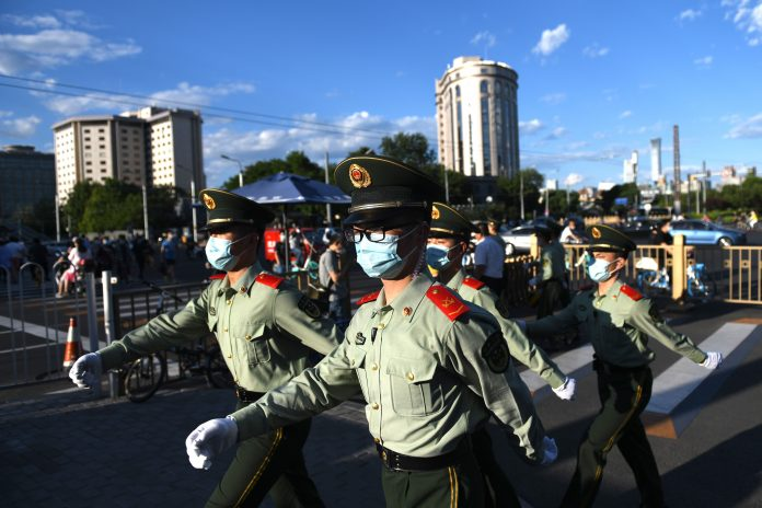 Paramilitary police officers patrol along a street after the closing session of the Chinese People's Political Consultative Conference (CPPCC) in Beijing on May 27, 2020. (Image: GREG BAKER/AFP via Getty Images) journalists