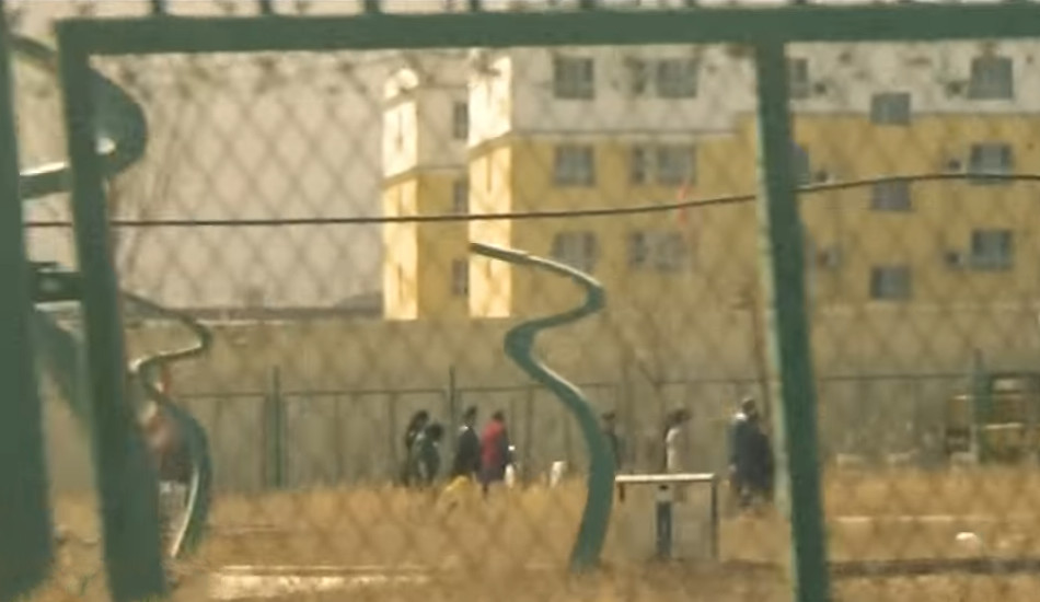 Uyghurs as seen through the fence at a detention center in Xinjiang, China.