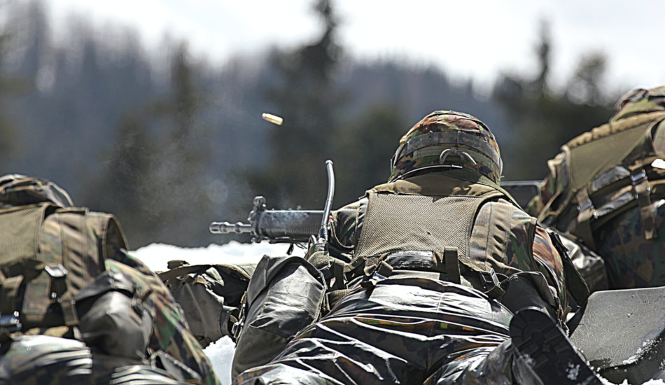 A soldier fires his weapon downrange.