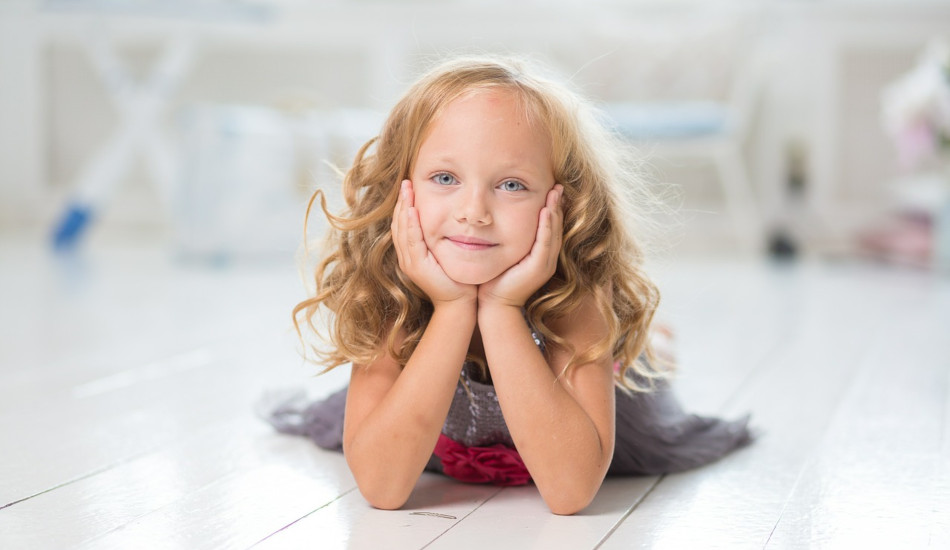 A girl lying on the floor an posing for the camera.