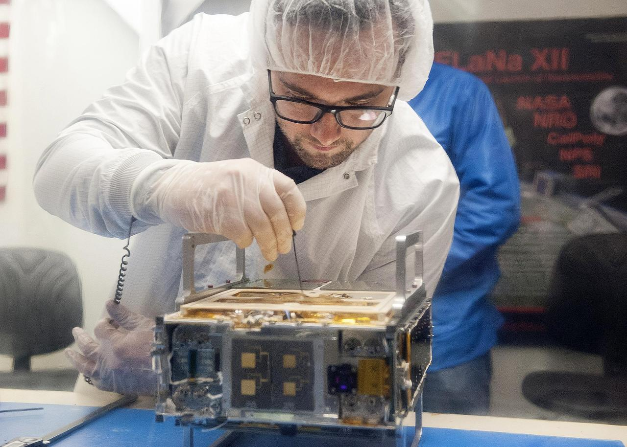 Engineer from JPL making adjustments to a CubeSat.