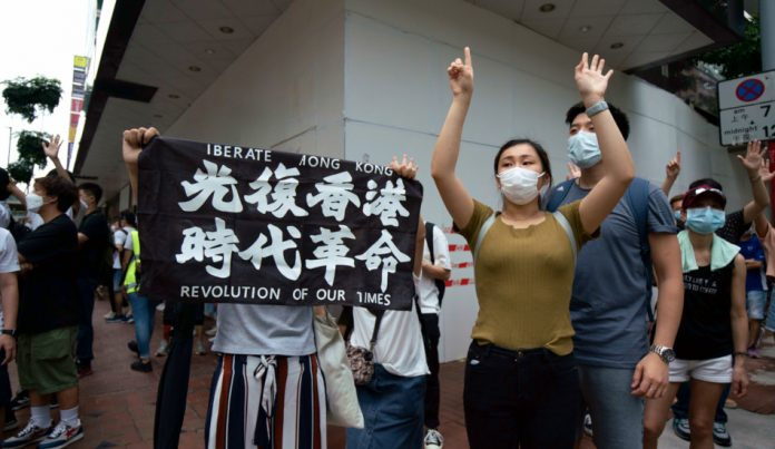 """Protesters in Hong Kong with a banner reading: """"Liberate Hong Kong, Revolution in Our Time""""."""
