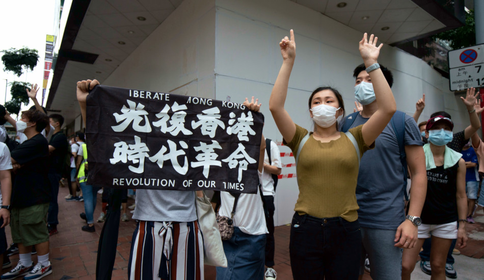"Protesters in Hong Kong with a banner reading: ""Liberate Hong Kong, Revolution in Our Time""."