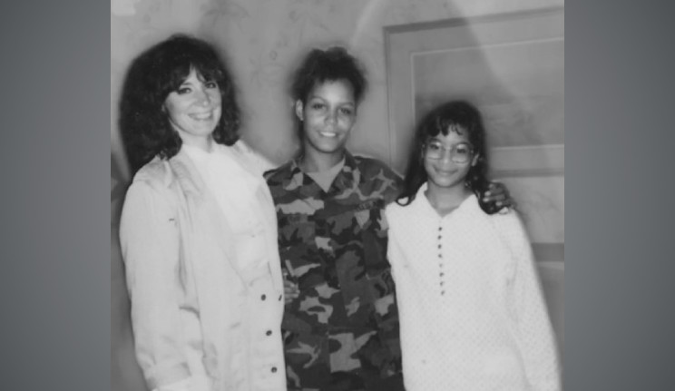 Mika as a child, posing with two women.