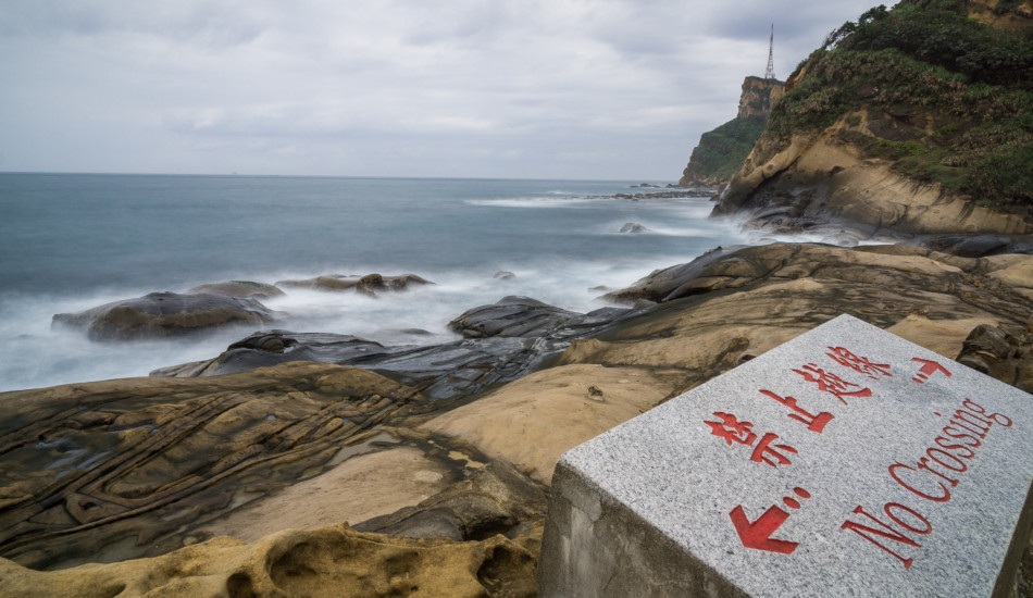 """A sign reads """"No Crossing"""" on a beach in Taiwan."""