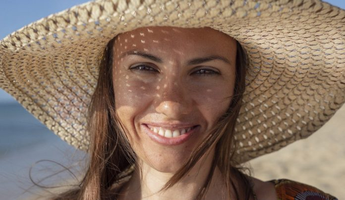 Smiling woman wearing a hat at the beach.
