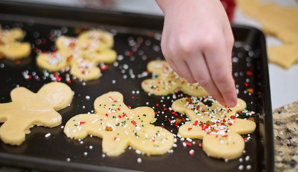 A child puts sprinkles on a tray of sugar cookies before they go in the oven.