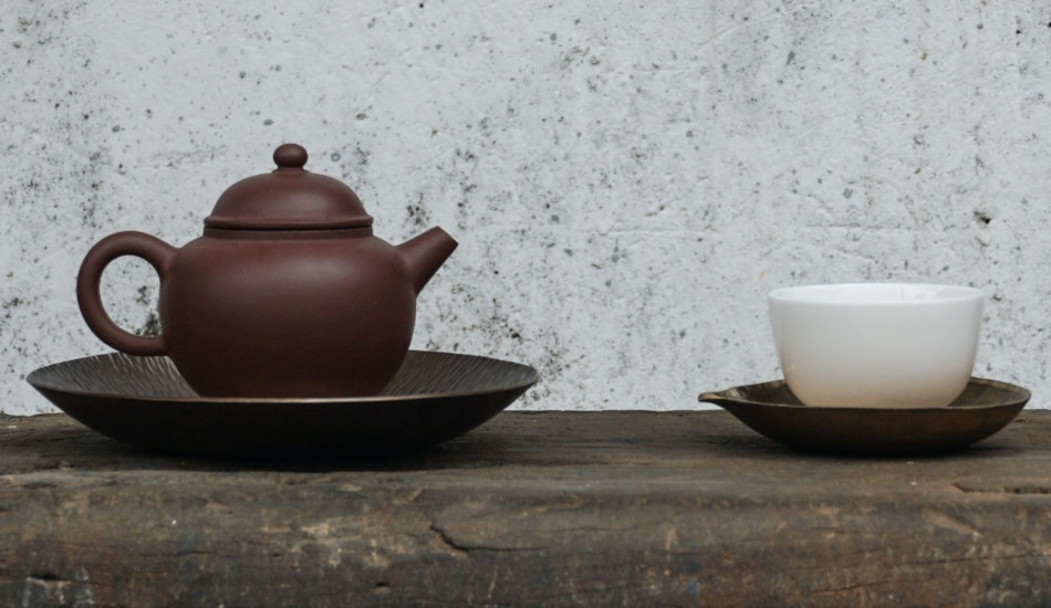 A teapot and cup sitting on a table.