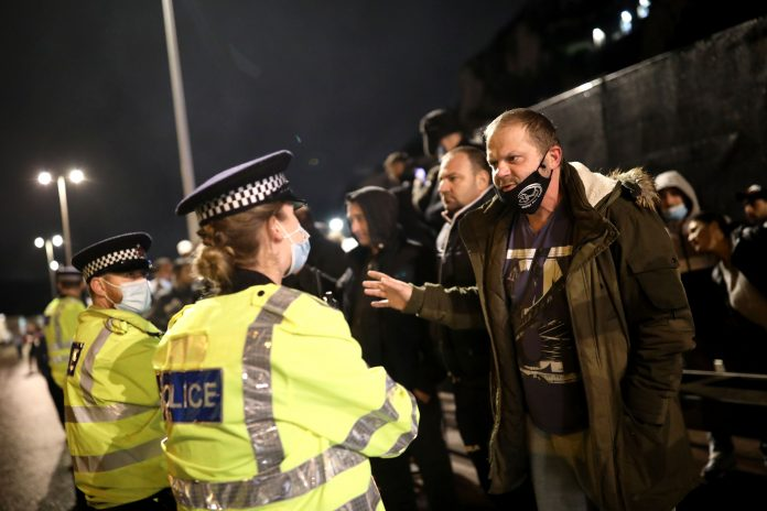 Police officers speak to a group of lorry drivers as the Port of Dover remains closed on December 22, 2020 in Dover, United Kingdom. Over 1500 lorries remained stacked up around Kent as drivers waited for a resumption of travel from the port of Dover to France. On Sunday, France abruptly halted freight and passenger travel from the UK over concerns about the UK's surging covid-19 cases and a new virus mutation.