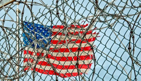 a us american flag waves on a clear day behind a chain link fence barbed wire justice department