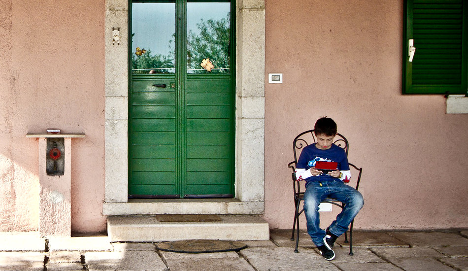 A boy sits outside playing a video game.