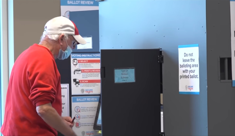 A man uses a voting machine.