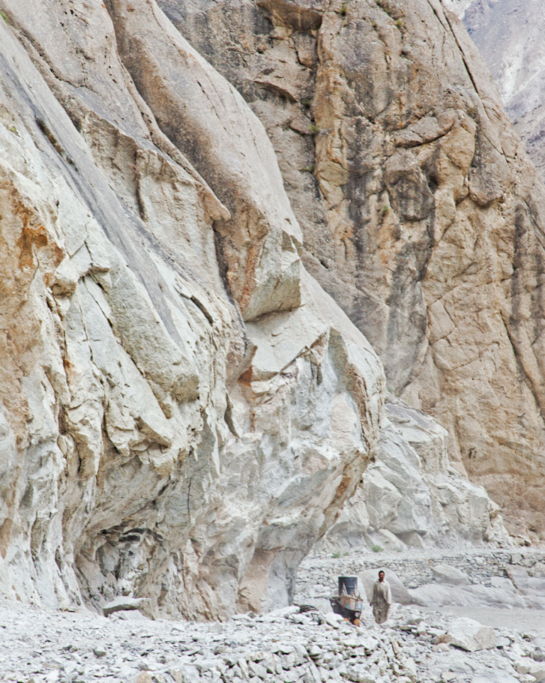 A lone hunter prepares to work on a cliff face in the mountains of Dassu.