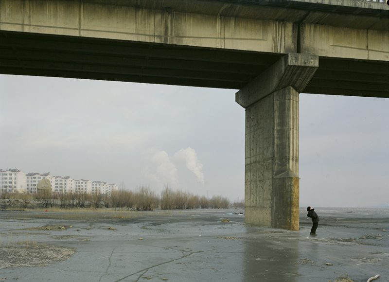 A man doing his morning exercises under a bridge, in China.