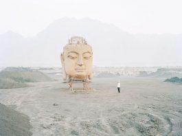 A Buddha head sculpture in a coal yard in Ningxia as man watches on.by Yellow River Photographer Zhang Kechun
