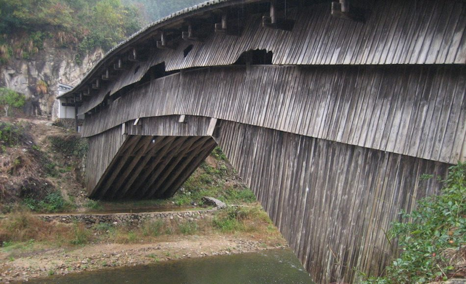 A wooden bridge in china over river named rainbow bridge.