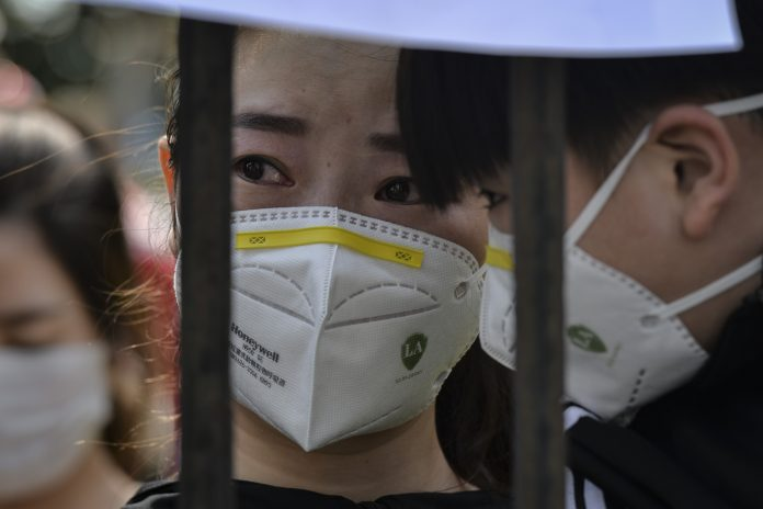 This photo taken on March 18, 2020 shows a resident reacting as members of a medical assistance team from Yunnan province depart after helping with the COVID-19 coronavirus recovery effort in Wuhan, in China's central Hubei province. (Image: STR/AFP via Getty Images)