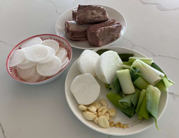 Bowls containing Korean radish, beef, garlic, and leeks.