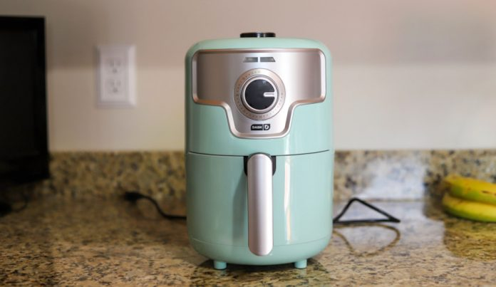 A 2qt Dash air fryer in aqua on a kitchen counter.