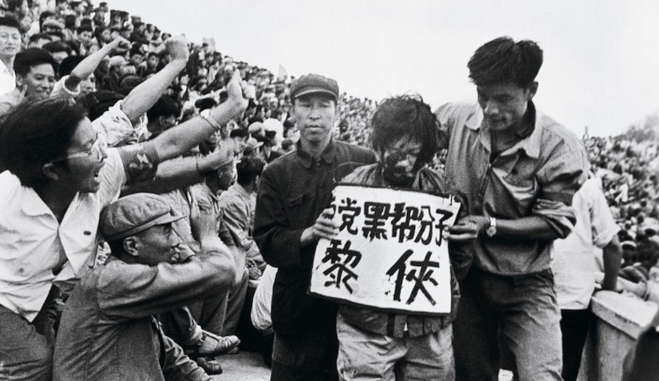 A scholar with ink-splattered face undergoes public humiliation during the Cultural Revolution in China.