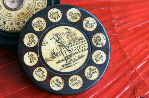 Antique Chinese Zodiac Wheel with feng shui compass made of engraved bone and wood on red fan background