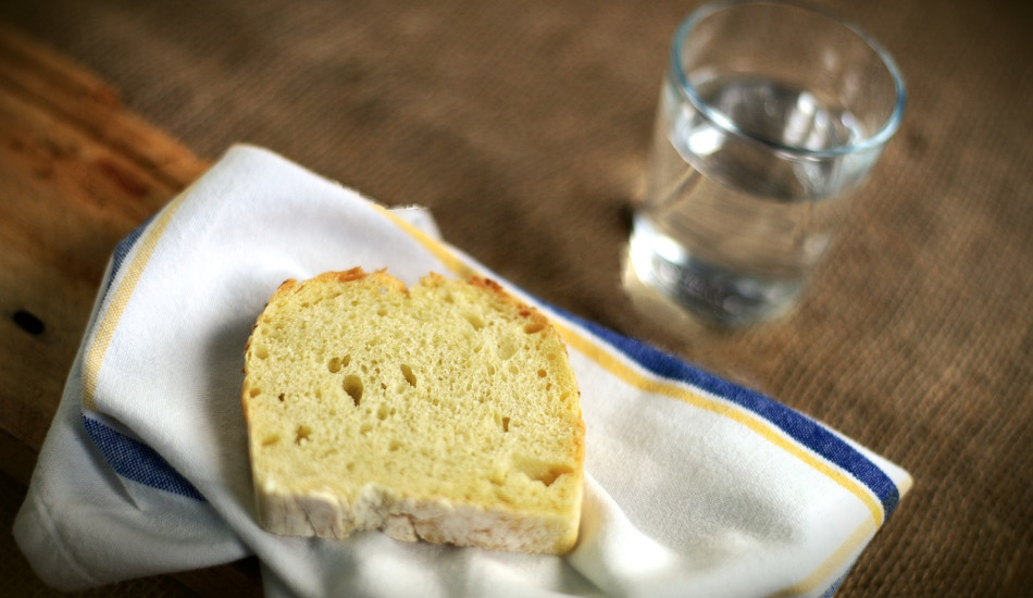 A piece of bread and a glass of water.