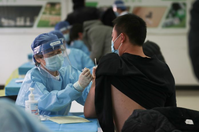 A medical worker (L) administers a Covid-19 coronavirus vaccine to a man at a temporary vaccination center in Beijing on January 8, 2021. (Image: STR/CNS/AFP via Getty Images)