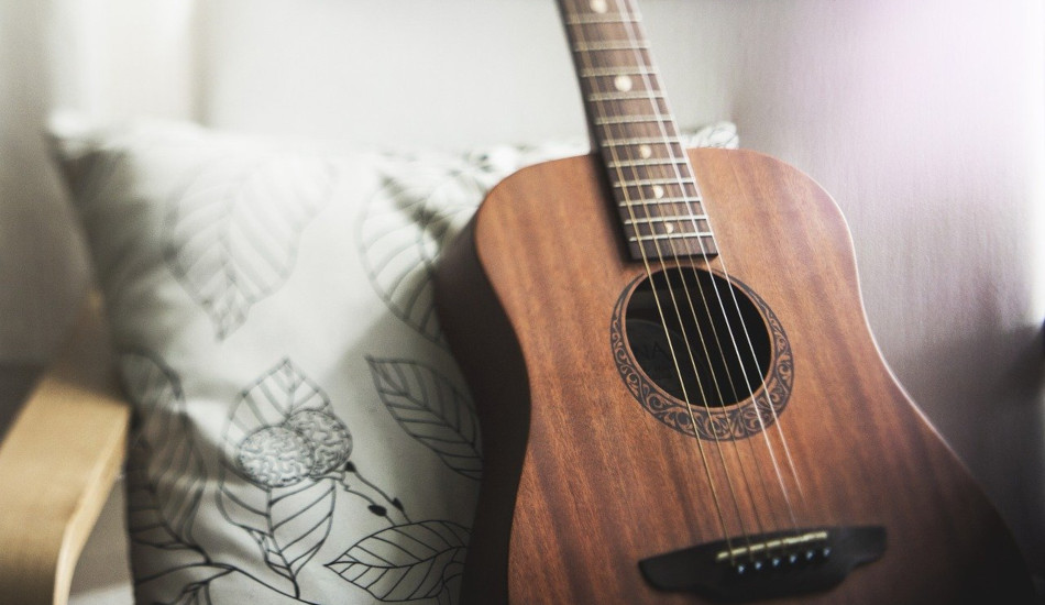 A guitar propped up against a pillow.