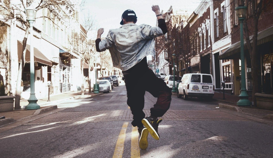 A young man dances in the middle of the street.